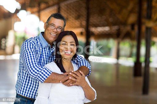 istock Cheerful mature latin couple looking at camera 614954714