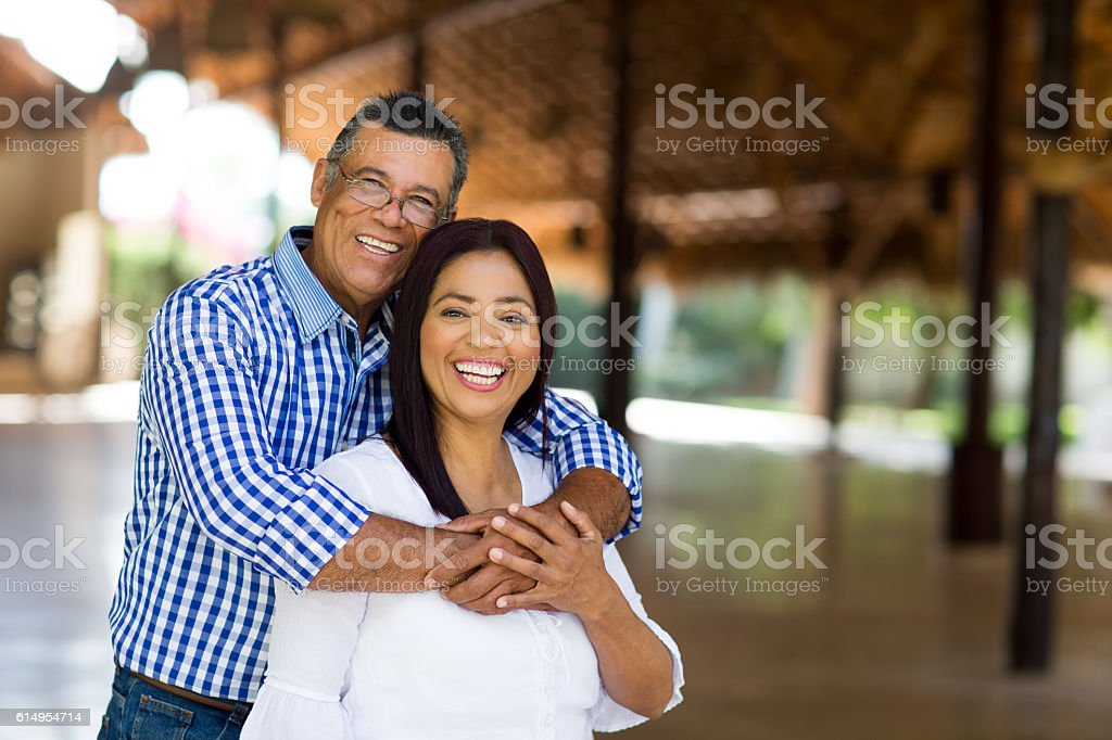 Cheerful mature latin couple looking at camera stock photo