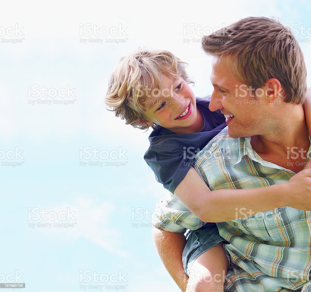 Cheerful mature man carrying his son on back against sky stock photo