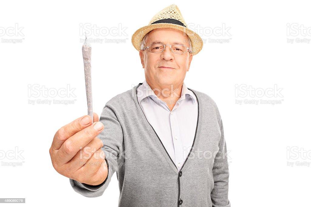 Cheerful mature man holding medicinal marijuana stock photo