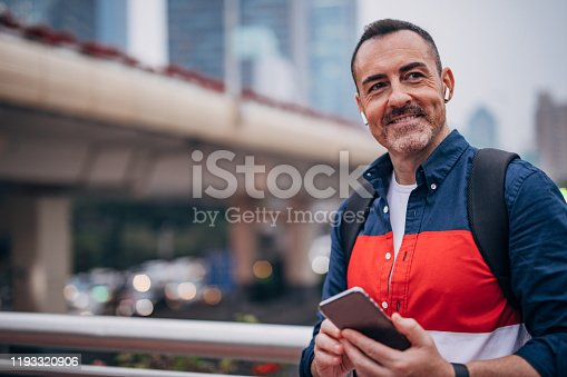Mature man with backpack is using wireless headset and mobile phone.