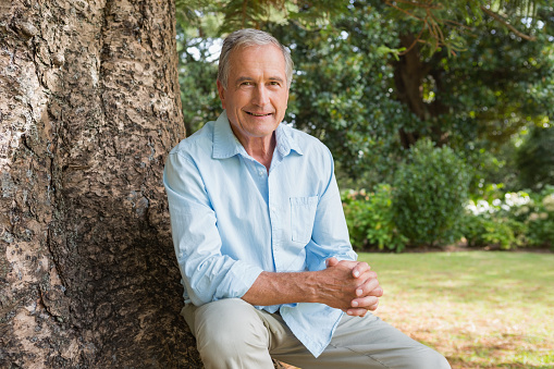 Cheerful mature man sitting on tree trunk