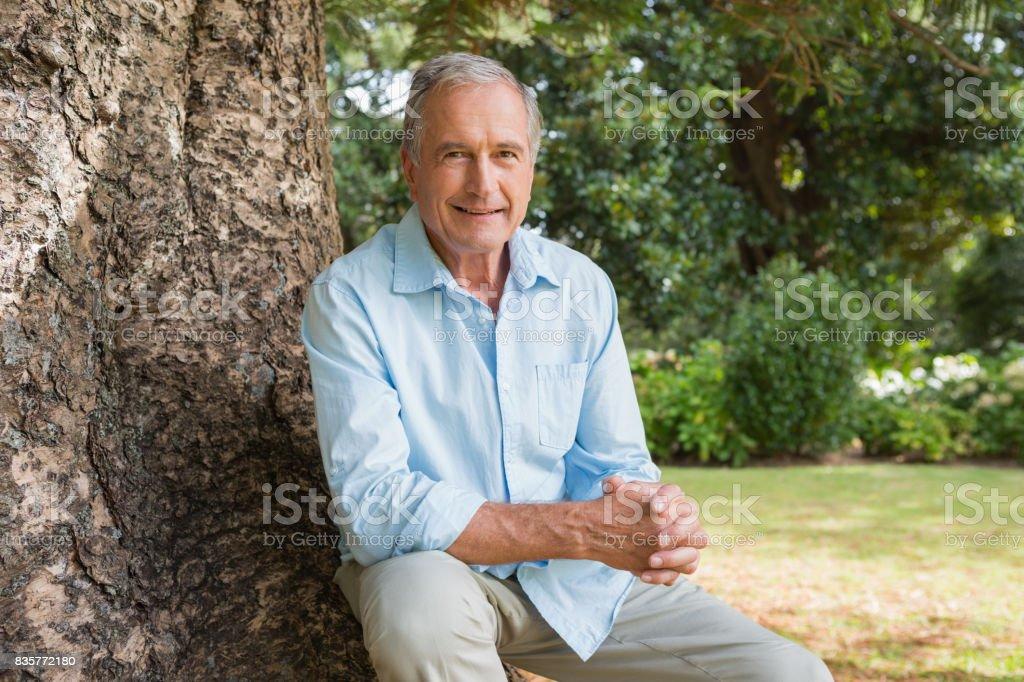 Joyeux homme d'âge mûr assis sur le tronc d'arbre - Photo