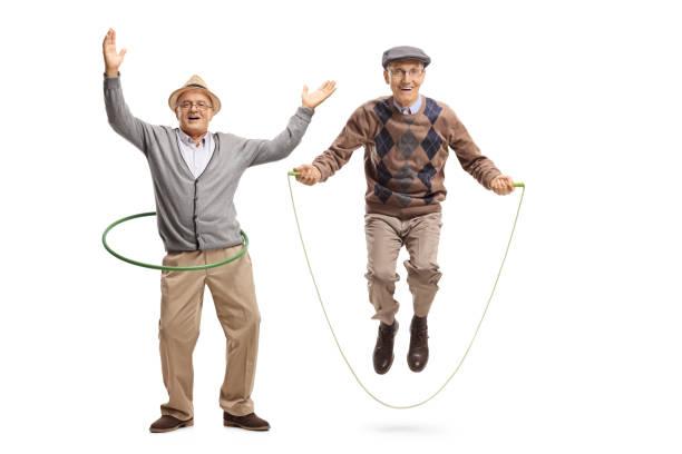 fröhliche reifer mann mit einem hula hoop reifen und ein senior mann auf einem springseil springen - hula hoop workout stock-fotos und bilder
