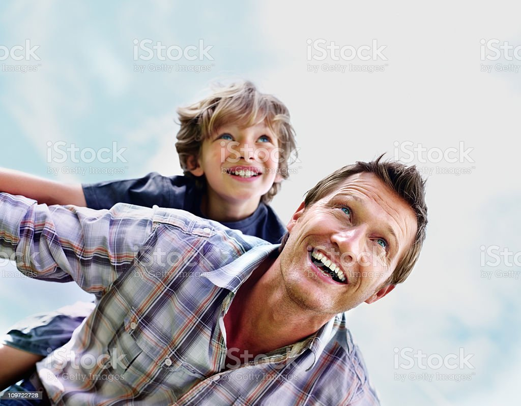 Cheerful mature man with son on back flying against sky royalty-free stock photo