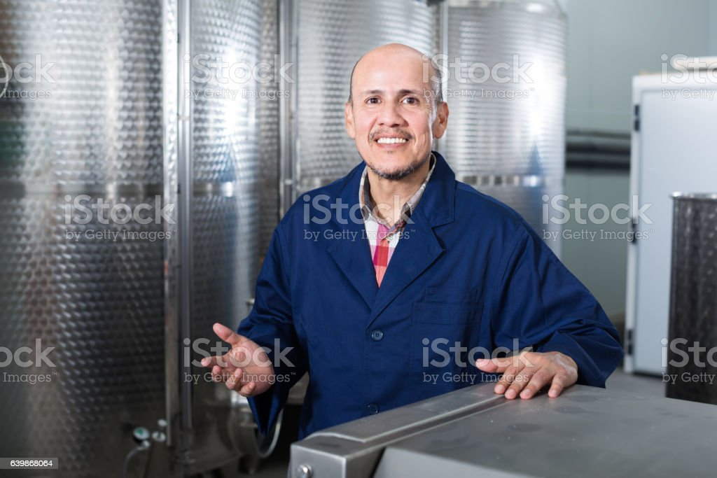 Cheerful mature man working in wine secondary fermentation secti stock photo