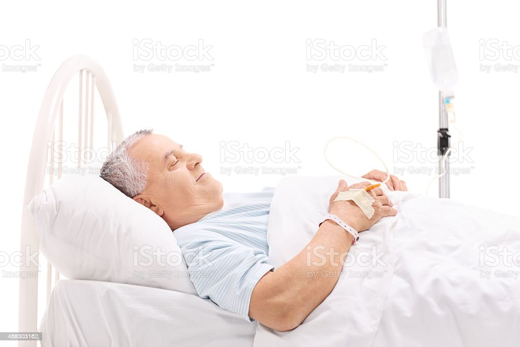 Cheerful mature patient lying in a hospital bed stock photo