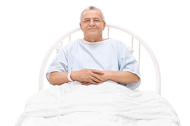 cheerful mature patient lying in a hospital bed - hospital studio bildbanksfoton och bilder