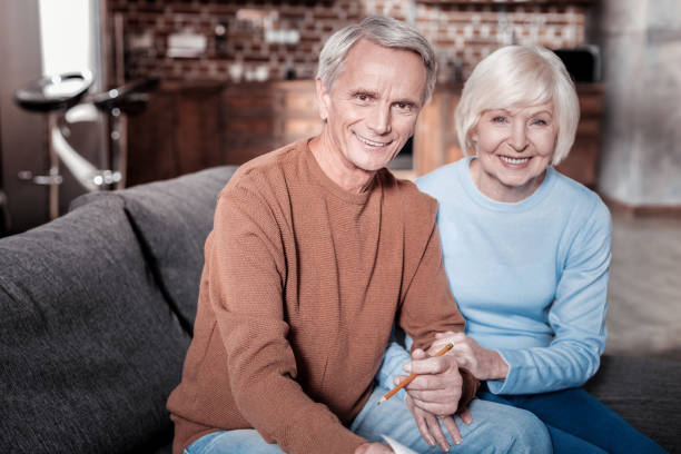 cheerful mature people sitting on the sofa - baby boomers stock pictures, royalty-free photos & images
