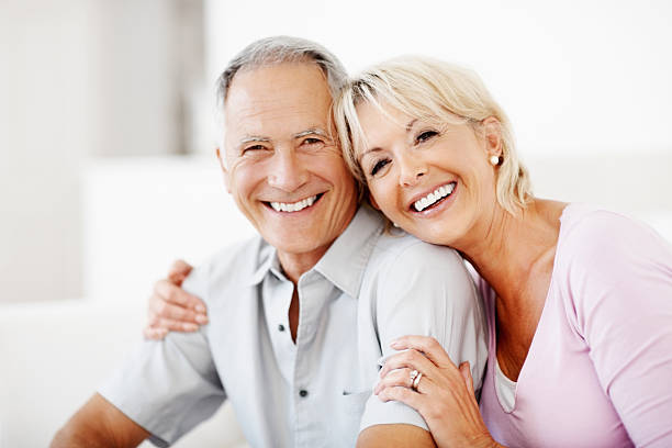 cheerful mature woman embracing senior man against white - midsection stock pictures, royalty-free photos & images