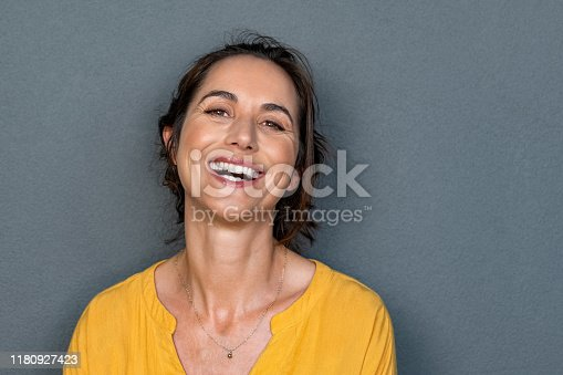 Portrait of mature woman laughing against grey background. Successful middle aged woman in casual clothing with toothy smile looking at camera. Cheerful happy young beautiful latin lady smiling with copy space.