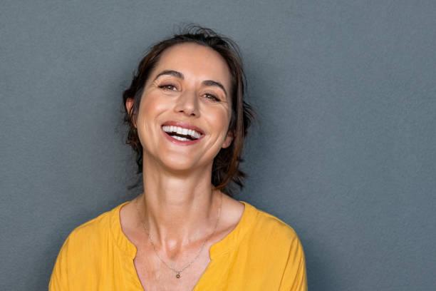 sourire mûr de femme gai - femmes d'âge mûr photos et images de collection