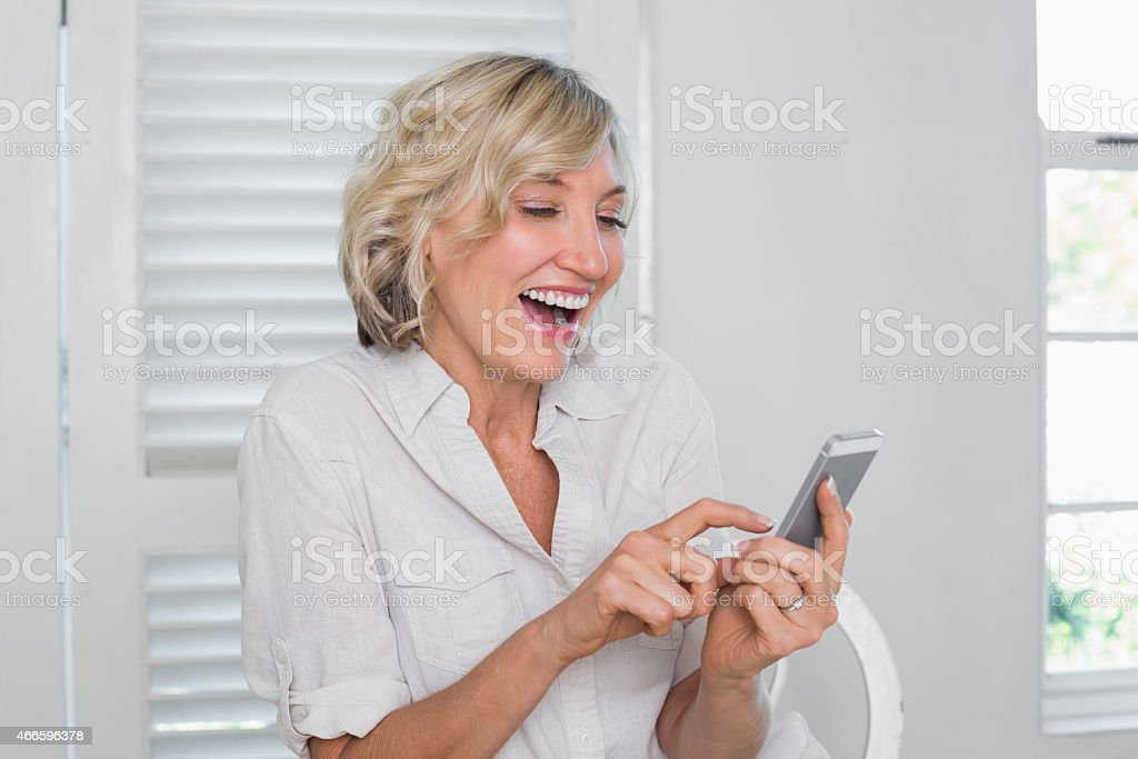 Cheerful mature woman text messaging stock photo
