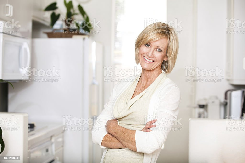 Cheerful mature woman with arms crossed royalty-free stock photo