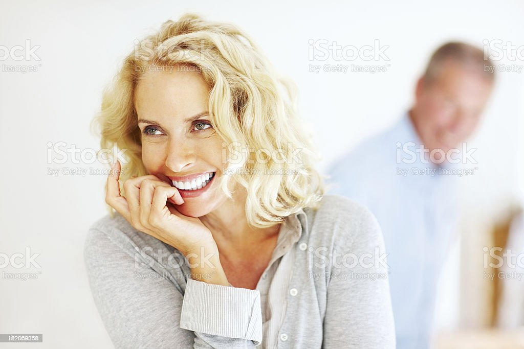 Cheerful mature woman with man in background stock photo