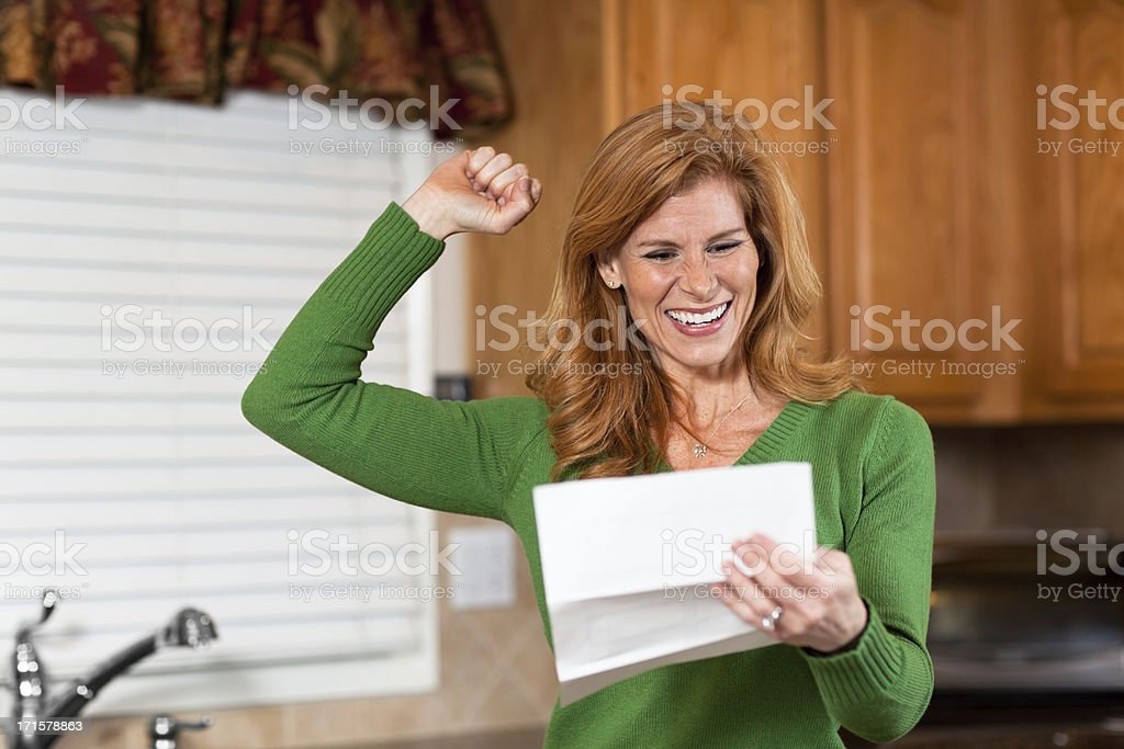 Cheerful mature woman with raised hand reading letter royalty-free stock photo