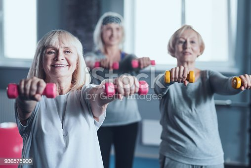 936573360 istock photo Cheerful mature women using dumbbells while exercising at fitness club 936575900