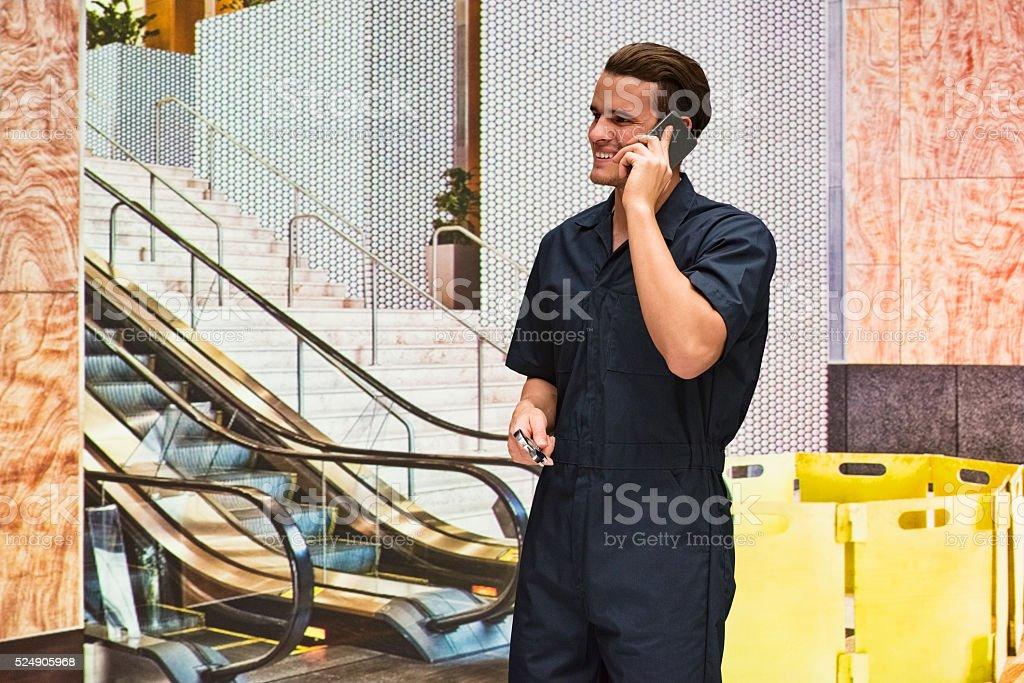 Cheerful mechanic on phone in office stock photo