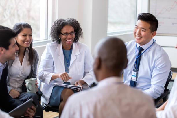 os colegas de trabalho médicos alegres apreciam a reunião do pessoal - profissional da área médica - fotografias e filmes do acervo