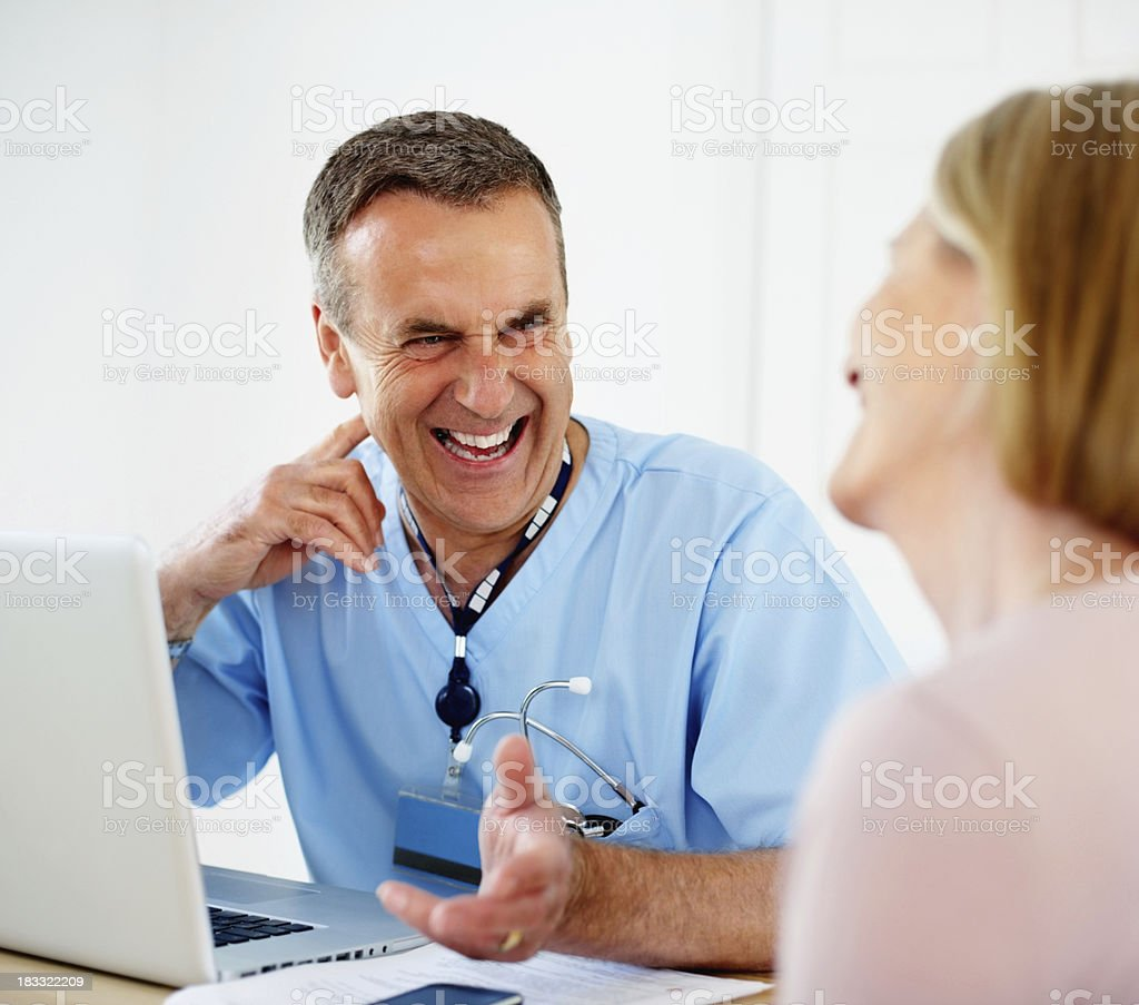 Cheerful medical doctor talking to female patient royalty-free stock photo