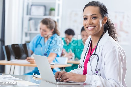 Beautiful African American female medical intern uses a laptop during class. She is smiling at the camera.
