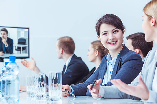 Cheerful member of the management staff Cheerful young manager looking straight into the camera, surrounded by her colleagues at a conference table governing board stock pictures, royalty-free photos & images