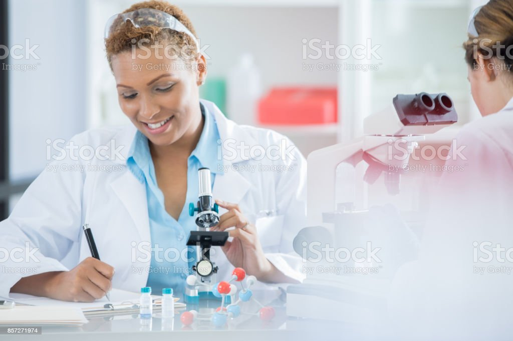 A smiling mid adult female lab technician sits at a table opposite an...