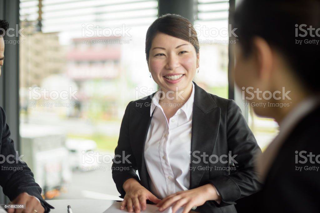 Cheerful mid adult Japanese businesswoman smiling stock photo