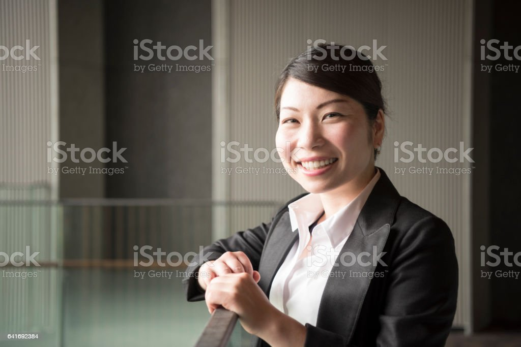 Cheerful mid adult Japanese businesswoman smiling towards camera stock photo