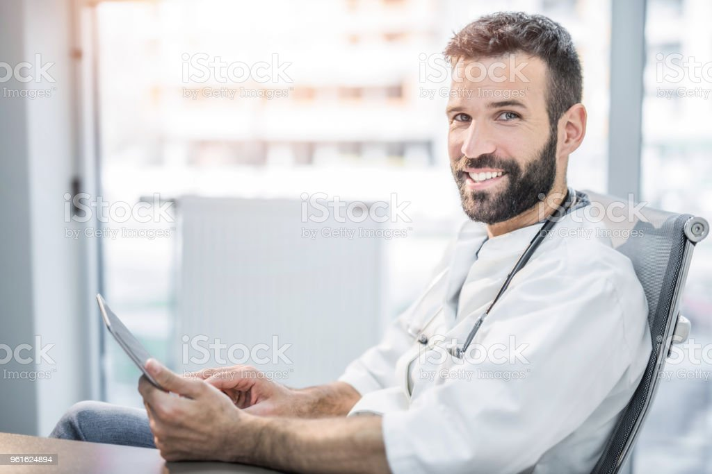 Cheerful mid adult male doctor smiling at camera while using tablet. stock photo