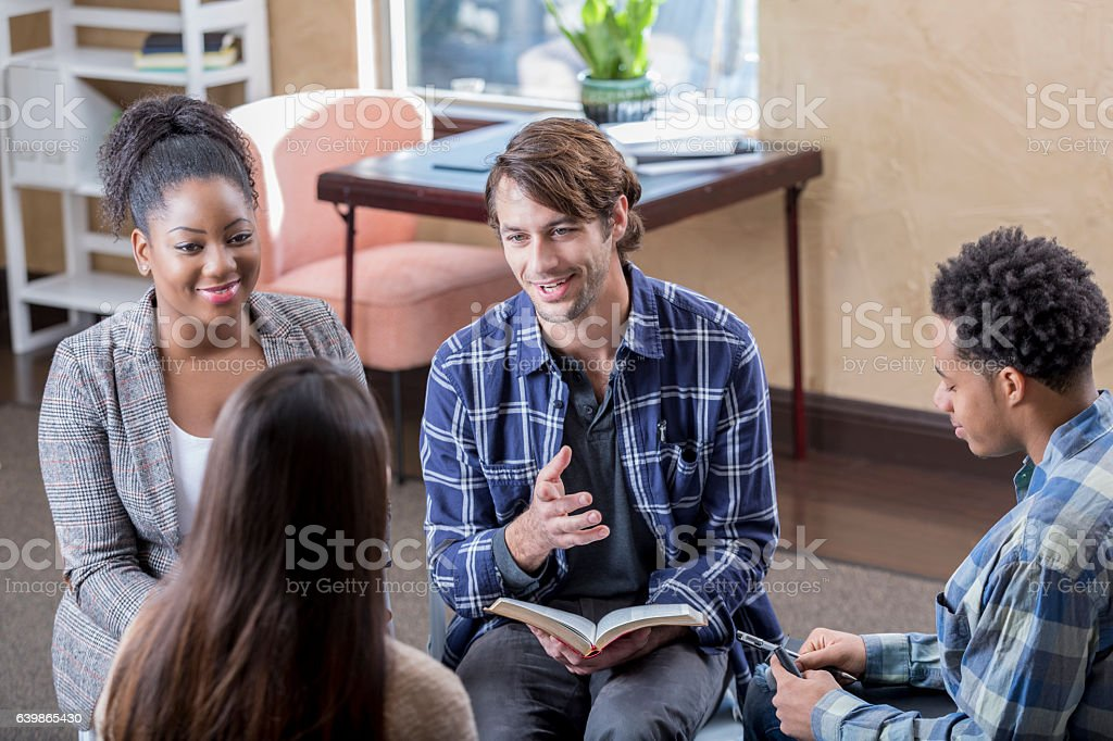 Cheerful mid adult man leads Bible study stock photo