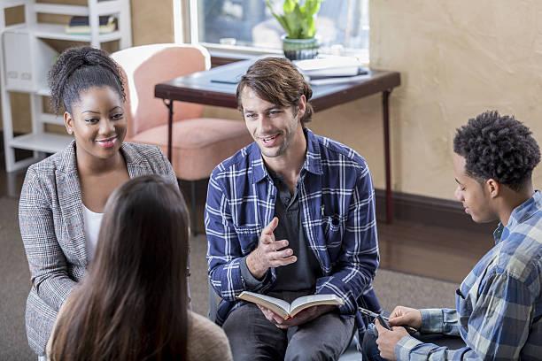 cheerful mid adult man leads bible study - geführtes lesen stock-fotos und bilder