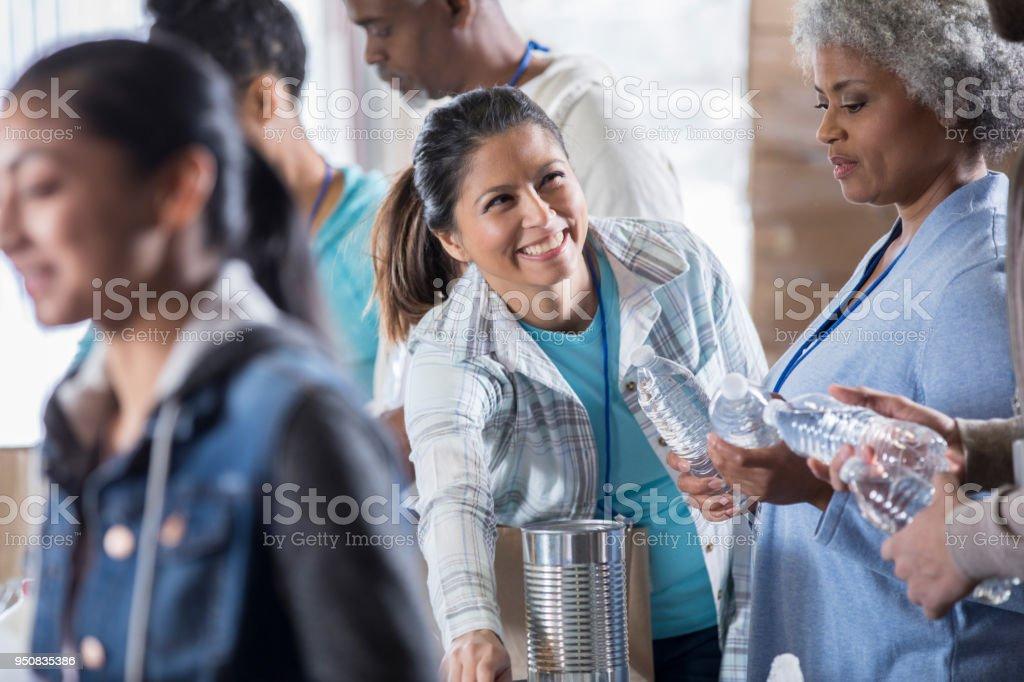 Cheerful mid adult woman enjoys volunteering at food bank stock photo