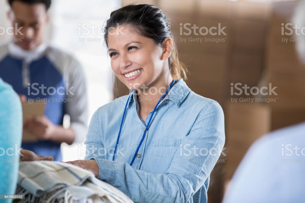 Cheerful mid adult woman passes out blankets during distaster relief stock photo