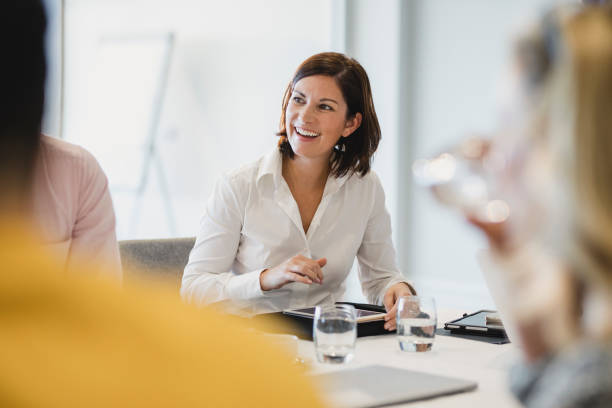 Cheerful mid adult woman smiling at business meeting Businesswoman smiling at meeting table, listening, learning, success, happiness real life stock pictures, royalty-free photos & images