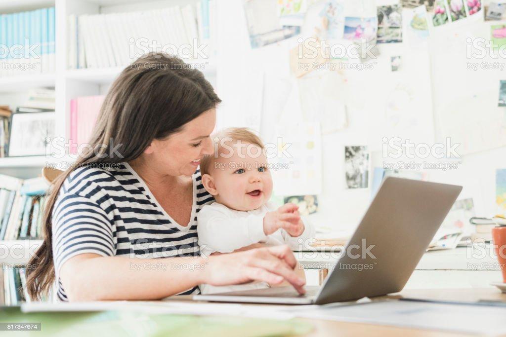 Fröhlich Mitte Erwachsene Frau Mit Baby Auf Schoß Mit Computer