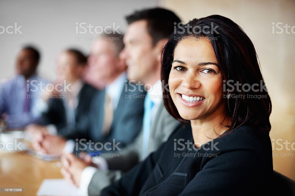Cheerful middle aged business woman with blur team in meeting royalty-free stock photo