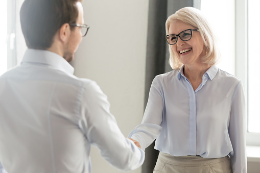 Cheerful middle aged businesswoman handshaking greeting new employee