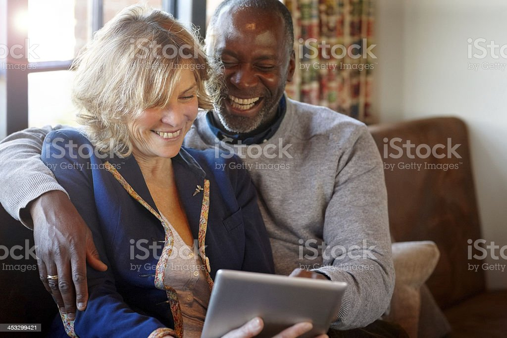 Cheerful middle aged couple in a restaurant using digital tablet - Royalty-free 50-59 Years Stock Photo