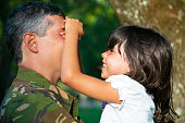 Cheerful military father holding little daughter in arms while joyful girl shutting his and smiling. Side view. Family reunion or returning home concept