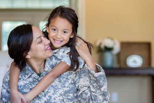 Little girl rides piggyback on her mom's back. Her mom has just returned from military assignment.
