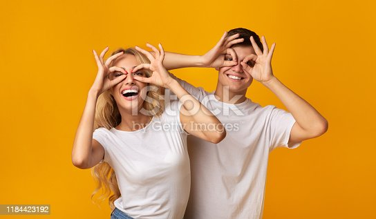 1092709104istockphoto Cheerful millennial couple fooling together making funny glasses with fingers 1184423192