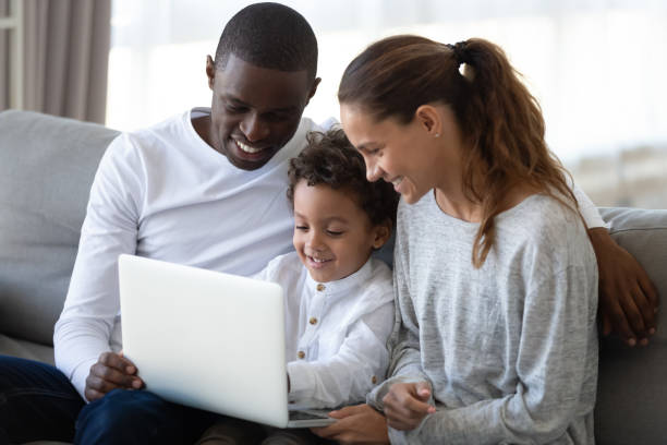 Cheerful mixed race family sitting on sofa, holding laptop. Cheerful mixed race family sitting together on comfortable sofa in living room, holding laptop on knees, looking at screen, playing online game, watching movie or cartoons, shopping in internet store. mixed race person stock pictures, royalty-free photos & images