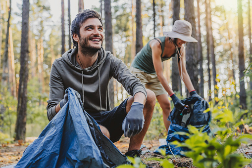 Cheerful mixed race man looking away while collecting trash with friends outdoor