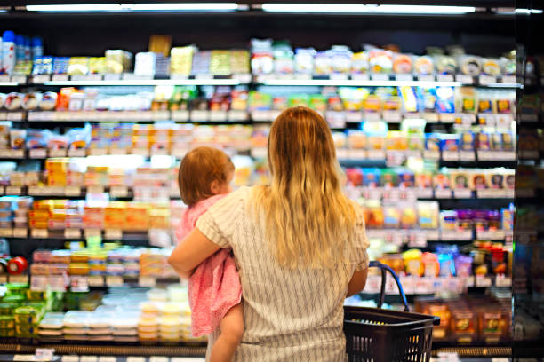 Cheerful mother and baby spending time in shopping in supermarket stock photo