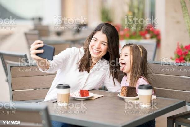 Cheerful mother and daughter at cafe taking selfie picture id921976508?b=1&k=6&m=921976508&s=612x612&h=akezvwigmkyowllpucgytdqzykhmkvwgkutf r7diik=