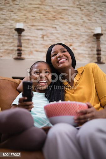 istock Cheerful mother and daughter enjoying television at home 800477002