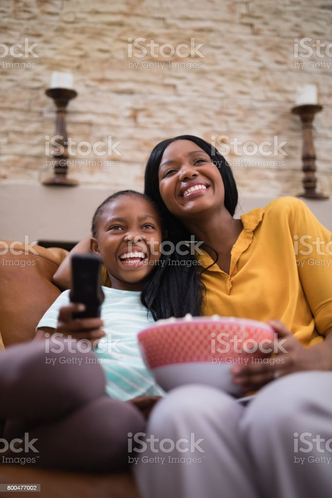 Cheerful mother and daughter enjoying television at home stock photo