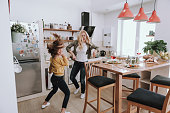 Full length portrait of charming blond woman spending time with her adorable kid. They dancing and laughing in kitchen