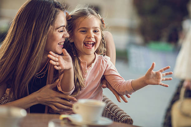 Cheerful mother and daughter having fun together in a cafe. stock photo